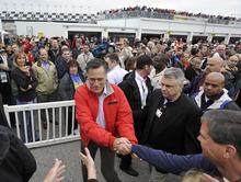Republican presidential candidate, former Massachusetts Gov. Mitt Romney, center, greets fans as he walks through the garage area before the NASCAR Daytona 500 Sprint Cup series auto race at Daytona International Speedway in Daytona Beach, Fla., Sunday, Feb. 26, 2012. (AP Photo/Rainier Ehrhardt)