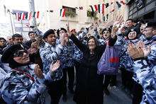 A Syrian woman, center, dances between pro-Syrian regime supporters wearing police uniforms as they celebrate outside a polling station during a referendum on the new constitution, in Damascus, Syria, Sunday, Feb. 26, 2012. Syrians began voting Sunday on a new draft constitution aimed at quelling the country's uprising by ending the ruling Baath Party's five-decade domination of power, but the opposition announced a boycott and clashes were reported across the country. (AP Photo/Muzaffar Salman)