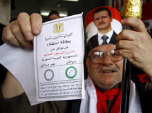 A Syrian man holds up his ballot paper at a polling station during a referendum on the new constitution in Damascus, Syria, on Sunday Feb. 26, 2012. Syrians began voting Sunday on a new draft constitution aimed at quelling the country's uprising by ending the ruling Baath Party's five-decade domination of power, but the opposition announced a boycott and clashes were reported across the country. Arabic on the ballot Paper reads,
