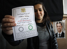 A Syrian woman shows her ballot paper at a polling station during a referendum on the new constitution, in Damascus, Syria, Sunday, Feb. 26, 2012. Syrians began voting Sunday on a new draft constitution aimed at quelling the country's uprising by ending the ruling Baath Party's five-decade domination of power, but the opposition announced a boycott and clashes were reported across the country. Arabic on the ballot Paper reads,
