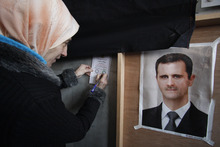 A Syrian woman fills a ballot paper next to a portrait of Syrian President Bashar Assad at a polling station during a referendum on the new constitution in Damascus, Syria, Sunday Feb. 26, 2012. Syrians began voting Sunday on a new draft constitution aimed at quelling the country's uprising by ending the ruling Baath Party's five-decade domination of power, but the opposition announced a boycott and clashes were reported across the country. (AP Photo/Muzaffar Salman)