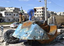 In this Tuesday, Feb. 21, 2012 photo, Syrian girls play on top of a destroyed Syrian riot police tank at Bayada neighborhood in Homs province, Syria. Syrians began voting Sunday on a new draft constitution aimed at quelling the country's uprising by ending the ruling Baath Party's five-decade domination of power, but the opposition announced a boycott and clashes were reported across the country. In regions like the restive central city of Homs, where shelling by government forces has left hundreds dead, or the northwestern province of Idlib and the southern region of Daraa where rebels clash frequently with the security forces, turnout is likely to be minimal. (AP Photo)