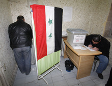 A Syrian man, left, signs ballot papers inside a voting booth at a polling station during a referendum on the new constitution in Damascus, Syria, Sunday Feb. 26, 2012. Syrians began voting Sunday on a new draft constitution aimed at quelling the country's uprising by ending the ruling Baath Party's five-decade domination of power, but the opposition announced a boycott and clashes were reported across the country. In regions like the restive central city of Homs, where shelling by government forces has left hundreds dead, or the northwestern province of Idlib and the southern region of Daraa where rebels clash frequently with the security forces, turnout is likely to be minimal. (AP Photo/Muzaffar Salman)