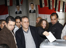 A Syrian woman casts her ballot paper at a polling station during a referendum on the new constitution, in Damascus, Syria, Sunday Feb. 26, 2012. Syrians began voting Sunday on a new draft constitution aimed at quelling the country's uprising by ending the ruling Baath Party's five-decade domination of power, but the opposition announced a boycott and clashes were reported across the country. In regions like the restive central city of Homs, where shelling by government forces has left hundreds dead, or the northwestern province of Idlib and the southern region of Daraa where rebels clash frequently with the security forces, turnout is likely to be minimal. (AP Photo/Muzaffar Salman)