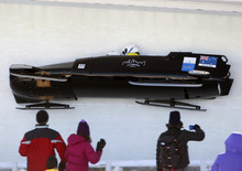 Australia's pilot Heath Spence, with pushers Gareth Nichols, Ben Lisson and brakeman Lucas Mata, crash in the third heat in the men's four-man Bobsled World Championships in Lake Placid, N.Y., on Sunday, Feb. 26, 2012. (AP Photo/Mike Groll)