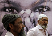 Indian riot victims look on as they stand in front of a poster during a ceremony in Ahmedabad, India, Monday, Feb. 27, 2012. Hundreds of survivors of deadly religious riots gathered in western India on Monday to mark the 10th anniversary of the country's worst sectarian violence in recent years even as rights groups blasted the local government for delaying justice. On Feb. 27, 2002, a train fire in Gujarat state killed 60 Hindu pilgrims. Muslims were blamed for the fire and weeks of rioting followed. More than 1,000 people, almost all Muslim, were killed as Hindu mobs rampaged through towns and villages. (AP Photo/Ajit Solanki)