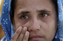 An Indian riot victim wipes her tears during a ceremony in Ahmedabad, India, Monday, Feb. 27, 2012. Hundreds of survivors of deadly religious riots gathered in western India on Monday to mark the 10th anniversary of the country's worst sectarian violence in recent years even as rights groups blasted the local government for delaying justice. On Feb. 27, 2002, a train fire in Gujarat state killed 60 Hindu pilgrims. Muslims were blamed for the fire and weeks of rioting followed. More than 1,000 people, almost all Muslim, were killed as Hindu mobs rampaged through towns and villages. (AP Photo/Ajit Solanki)