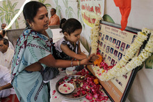 An Indian woman and a girl pay floral tribute to a photograph of Hindu pilgrims in Ahmedabad, India, Monday, Feb. 27, 2012. Hundreds of survivors of deadly religious riots gathered in western India on Monday to mark the 10th anniversary of the country's worst sectarian violence in recent years even as rights groups blasted the local government for delaying justice. On Feb. 27, 2002, a train fire in Gujarat state killed 60 Hindu pilgrims. Muslims were blamed for the fire and weeks of rioting followed. More than 1,000 people, almost all Muslim, were killed as Hindu mobs rampaged through towns and villages. (AP Photo/Ajit Solanki)