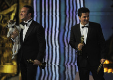 Jean Dujardin holds Uggie after accepting the Oscar for best picture  for