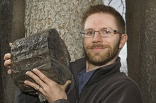Courtesy ISU Photographic Services Dr. Leif Tapanila holding a petrified log containing 210 million year old beetle borings from Wolverine Petrified Forest, Grand Staircase-Escalante National Monument, Utah.