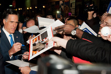 Republican presidential candidate Mitt Romney signs autographs after taping an episode of the