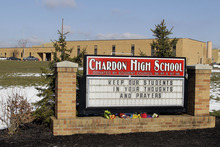 Bouquets of flowers sit on the sign in front of the high school in Chardon, Ohio Tuesday, Feb. 28, 2012. A gunman opened fire inside the school's cafeteria at the start of the school day Monday. Two of the victims have died and three remain hospitalized  (AP Photo/Mark Duncan)