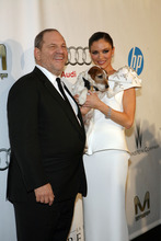 Harvey Weinstein and his wife Georgina Chapman with Uggie the dog pose at the Weinstein Company Post-Oscar Party on Sunday, Feb. 26, 2012, in West Hollywood, Calif.  (AP Photo/Ringo H.W. Chiu)
