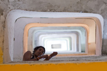 In this Feb. 23, 2012 photo, a woman looks down from the staircase in the occupied Prestes Maia building in downtown Sao Paulo, Brazil.  Occupied in 2002 by about 350 homeless families, the building lacks electricity, elevators and running water. The families are part of Brazil's