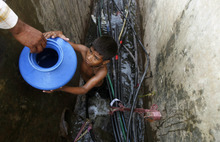 A young boy collects water from a broken pipe in a slum in Mumbai, India, Wednesday, Feb. 29, 2012. Millions of children are growing up in squalid urban areas and are denied basic services despite living close to them, the United Nations Children's Fund said Tuesday. UNICEF said children living in slums and shantytowns often lack water, electricity and healthcare and urged policy makers to ensure urban planning meets the needs of children. (AP Photo/Rafiq Maqbool)