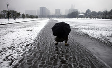 A man crouches on a snow-covered walkway outside the Imperial Palace in Tokyo, Wednesday, Feb. 29, 2012. Snow fall overnight covers the Metro area, causing delay of public transportation. (AP Photo/Junji Kurokawa)