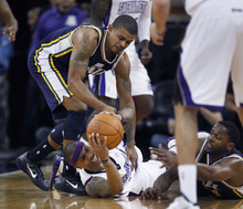 Sacramento Kings guard Isaiah Thomas vies for control of a loose ball against Utah Jazz defenders during the first half of an NBA basketball game in Sacramento, Calif., Tuesday, Feb. 28, 2012. (AP Photo/Steve Yeater)