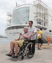A passenger of the Costa Allegra cruise ship in a wheelchair waits to board on a ferry at Victoria's harbor, Seychelles Island, Thursday, March 1, 2012.  Hot and tired passengers disembarking from the  disabled cruise ship Costa Allegra  Thursday in the Seychelles said they had prepared to abandon ship when fire broke out in the engine room three days ago, causing smoke to billow from the vessel that was suddenly adrift in waters prowled by pirates. (AP Photo/Gregorio Borgia)