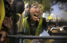 Detained Tibetan exiles shout slogans from inside a police van, outside the venue where the Chinese foreign minister is meeting with his Indian counterpart, in New Delhi, India, Thursday, March 1, 2012.  About a dozen Tibetan exiles protested as foreign ministers of China and India met in the Indian capital to improve ties between the Asian giants. Police detained the Tibetan exiles as they shouted