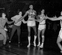 In this March 2, 1962, photo, fans and teammates rush onto court to congratulate Philadelphia Warriors Wilt Chamberlain (13) in Hershey, Pa., after he scored his 100th point in a 169-147 win over the New York Knickerbockers.  For 50 years, Chamberlain's 100-point night has stood as one of sports magic numbers. (AP Photo/File)