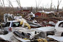 In this photo provided by SWAT Chasers via the Indianapolis Star, a man walks around a destroyed house looking for belongings in Henryville, Ind., Friday, March 2, 2012, after a series of powerful tornadoes tore through southern Indiana, killing at least 14 people and leaving several small towns in ruin. At least one person was confirmed dead in hard-hit Henryville. (AP Photo/SWAT Chasers, Chris Bergin via the Indianapolis Star)