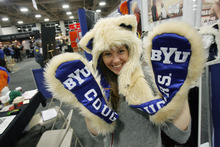Francisco Kjolseth  |  The Salt Lake Tribune Anne Nadel with Spirit Hoods based in L.A. CA, shows off one of the schools featured in their furry head and hand covers. The Campus Market Expo currently fills the Calvin L. Rampton Salt Palace Convention Center featuring 719 exhibitors in 1,491 booths showing off the latest tech stuff, celebration wears and sports gear being sold at college campus book stores around the country.