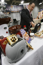 Francisco Kjolseth  |  The Salt Lake Tribune Joshua Fink, founder and CEO of Pangea Brands, whips up a Green Bay Packer waffle as he is surrounded by other gadgets including his various toasters featuring a slew of school emblems that can be toasted on your bread. The Campus Market Expo currently fills the Calvin L. Rampton Salt Palace Convention Center featuring 719 exhibitors in 1,491 booths showing off the latest tech stuff, celebration wears and sports gear being sold at college campus book stores around the country.