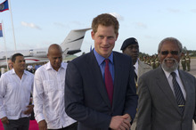Britain's Prince Harry as he arrives at Philip Goldson International Airport, Ladyville, Belize, where he was met by the Governor General of Belize, Sir Colville Young at the start of his tour to mark the Queen's Diamond Jubilee, Friday March 2, 2012.  Harry will spend the next seven days visiting three of his grandmother's realms of Belize, Bahamas and Jamaica, in honour of her 60-year reign.  (AP Photo/Arthur Edwards)