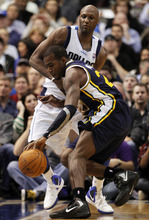 Utah Jazz forward Paul Millsap is defended by Dallas Mavericks' Lamar Odom, left, during the first half of an NBA basketball game, Saturday, March 3, 2012, in Dallas. (AP Photo/LM Otero)