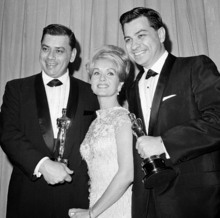 In this April, 5,1965 file photo actress Debbie Reynolds poses with Academy awards winners for best music Richard M. Sherman, right and Robert Sherman, left, who received the award for Mary Poppins in Santa Monica Calif. Songwriter  Sherman, who wrote the tongue-twisting