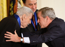 In this Nov. 17, 2008 file photo President George W. Bush, right, greets song writer Robert Sherman, in the East Room of the White House in Washington, as he presents him with the 2008 National Medals of Arts. Songwriter  Sherman, who wrote the tongue-twisting