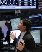 Seth Wenig  |  The Associated Press  A trader gestures on the floor at the New York Stock Exchange in New York on Tuesday. Stocks in the U.S. are down more than 1 percent at the opening bell, following similar declines in Europe.