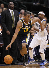 Utah Jazz guard Alec Burks (10) dribbles away from Dallas Mavericks' Jason Terry (31) as Jazz head coach Tyrone Corbin, rear left, looks on during the fourth quarter of an NBA basketball game in Dallas,  Saturday, March 3, 2012. The Mavericks won 102-96. (AP Photo/LM Otero)