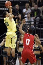 Oregon's Devoe Joseph, left, makes a 3-point shot over Utah's Chris Hines (0) during the first half of an NCAA college basketball game on Saturday, March 3, 2012, in Eugene, Ore. (AP Photo/Chris Pietsch)