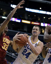 UCLA's Travis Wear (24) pulls in a rebound against Southern California's Garrett Jackson during the first half of an NCAA college basketball game at the Pac-12 conference tournament in Los Angeles, Wednesday, March 7, 2012. (AP Photo/Jae C. Hong)