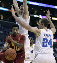 Southern California's Maurice Jones, left, passes the ball against UCLA's Travis Wear (2$) and David Wear, top, during the first half of an NCAA college basketball game at the Pac-12 Conference tournament in Los Angeles, Wednesday, March 7, 2012. (AP Photo/Jae C. Hong)
