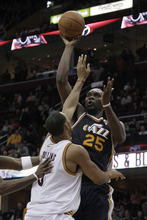 Utah Jazz's Al Jefferson (25) shoots over Cleveland Cavaliers' Ryan Hollins (5) in the second half of an NBA basketball game in Cleveland on Monday, March 5, 2012.  The Jazz won 109-100. (AP Photo/Amy Sancetta)
