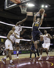 Utah Jazz's Gordon Hayward (20) splits the defense of Cleveland Cavaliers' Ramon Sessions (3), Alonzo Gee (33) and Tristan Thompson (13) for a basket in the first quarter of an NBA basketball game in Cleveland on Monday, March 5, 2012. (AP Photo/Amy Sancetta)