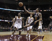 Utah Jazz's Devin Harris (5) flips the ball up for a shot in front of Cleveland Cavaliers' Alonzo Gee (33) and Anthony Parker (18) in the first quarter of an NBA basketball game in Cleveland on Monday, March 5, 2012. (AP Photo/Amy Sancetta)