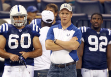 FILE- In this Aug. 19, 2011, file photo, Indianapolis Colts quarterback Peyton Manning, center, looks on next to teammates John Gill (60) and Jerry Hughes during the fourth quarter of an NFL preseason football game against the Washington Redskins in Indianapolis. Manning says he still holds out hope that he will be back on the field for the Colts this season. The four-time league MVP has not played a down since having neck surgery in May. (AP Photo/Michael Conroy, File)