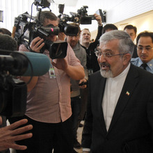 Iran's ambassador to the International Atomic Energy Agency, IAEA, Ali Asghar Soltanieh is surrounded by media and security when leaving the IAEA board of governors meeting at the International Center, in Vienna, Austria, on Thursday, March 8, 2012. (AP Photo/Ronald Zak)