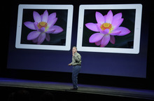 Apple's senior vice president of Worldwide Marketing Phil Schiller stands in front of an old iPad, left, and new iPad, right, during an Apple event in San Francisco, Wednesday, March 7, 2012.  The new iPad features a sharper screen and a faster processor.  Apple says the new display will be even sharper than the high-definition television set in the living room. (AP Photo/Paul Sakuma)