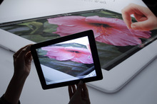 A new Apple iPad on display using the video during an Apple event in San Francisco, Wednesday, March 7, 2012.  The new iPad features a sharper screen and a faster processor.  Apple says the new display will be even sharper than the high-definition television set in the living room. (AP Photo/Paul Sakuma)