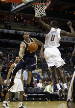 Utah Jazz guard Devin Harris, left, passes around Charlotte Bobcats center Bismack Biyombo, from the Republic of Congo, during the first half of an NBA basketball game on Wednesday, March 7, 2012, in Charlotte, N.C. (AP Photo/Nell Redmond)