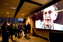 Kim Raff | The Salt Lake Tribune  People gather to watch a video of Richard Wirick during a memorial service for him at Gallivan Hall at Gallivan Plaza in Salt Lake City on March 8, 2012.