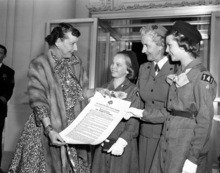 First lady Mamie Eisenhower, honorary president of the Girl Scouts of America, is given a scroll of thanks from the Scout organization in the White House in Washington, D.C., on March 6, 1956.  Making the presentation are, Margaret Solem, 11, Alexandria, Va., Mrs. Roy F. Layton, national president of the Girl Scouts, and Mary Sibert, 11, Alexandria, Va.  (AP Photo)