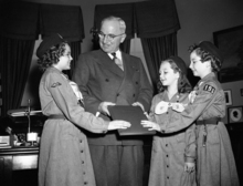 President Harry S. Truman receives a preparedness booklet from three Girl Scouts at the White House in Washington, Feb. 27, 1951. The girls, left to right are: Joyce Seyfried, Mary Lee Lankford and Janice Kauffman, all of Washington. (AP Photo/Henry Griffin)