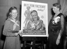 Mrs. Eleanor Roosevelt gazes from the Girl Scout War Bond poster to Betty Bredin who posed for the poster at the Girl Scoutsí Volunteer Leadership Dinner in New York on March 9, 1943. Miss Bredin is from Kew Gardens, N.Y. (AP Photo/Anthony Camerano)