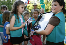 Tribune file photo  Ashley Wiltsie (left, holding flag), Amanda Wiltsie, Ciara Sase and Susie Eberle (far right) are excited to have been awarded a flag and plaque from the 4th Air Craft Maintenance Division of the 388th AMXS Unit. Girl Scout Troop 76 celebrated their bridging ceremony from Brownies into Junior Girl Scouts in June 2006. The bridging ceremony celebrates what the girls have accomplished from one Girl Scout  age level to the next.  For this troop, the bridging ceremony was extra special as two members of the Hill Air Force Base's 388th AMXS unit will be conducting a flag ceremony with the girls and present them with a U.S. flag that flew in Iraq on one of their missions.