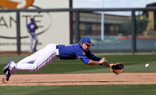 Texas Rangers third baseman Brandon Snyder makes a diving attempt for a single by Los Angeles Dodgers' Justin Sellers during the sixth inning of a spring training baseball game on Friday, March 9, 2012, in Surprise, Ariz. (AP Photo/Lenny Ignelzi)